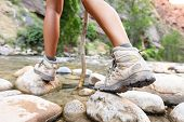stock photo of crossed legs  - Hiking shoes on hiker outdoors walking crossing river creek - JPG