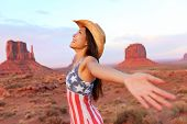 Cowgirl - woman happy and free in Monument Valley wearing cowboy hat with arms outstretched in freed