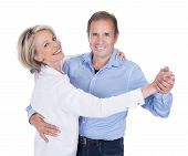 stock photo of waltzing  - Happy Mature Couple Dancing Isolated Over White Background - JPG