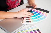 image of interior decorator  - Graphic designer working on a digital tablet in the background with pantone palette - JPG