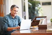 stock photo of maturity  - Mature Hispanic Man Using Laptop On Desk At Home - JPG