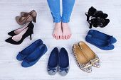 stock photo of shoes colorful  - Girl chooses shoes in room on grey background - JPG