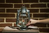 Hand lights a kerosene lamp on brick wall background