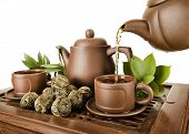 image of loam  - horizontal photo of the clay teapot tea flow in cup on white background isolated tea ceremony - JPG