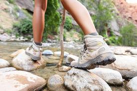 image of crossed legs  - Hiking shoes on hiker outdoors walking crossing river creek - JPG