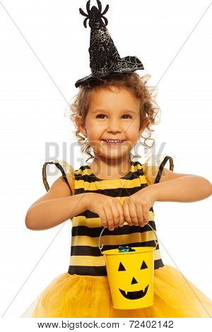 Little girl in bee costume with Halloween bucket
