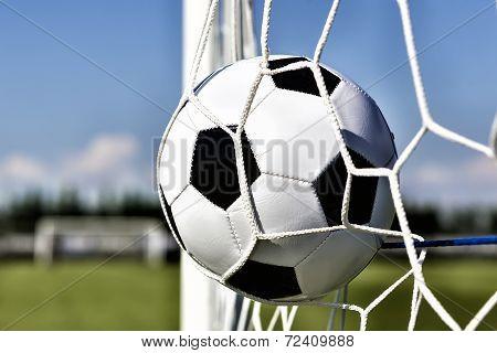 Soccer Football In Goal Net With Sky Field. Tonal Contrast