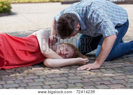Man Checking Pulse Of Fainted Girl