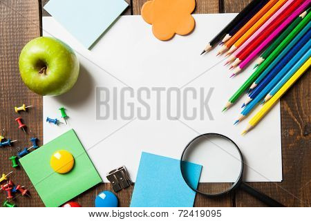 School supplies with blank on wooden background