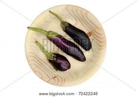 Three Eggplant On A Round Wooden Plate