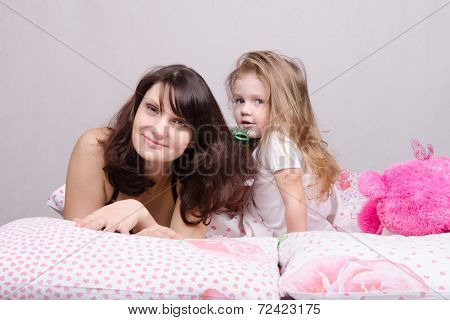 Mom And Daughter With A Hairbrush In Her Bed
