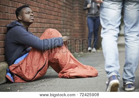 Homeless Teenage Boy In Sleeping Bag On The Street