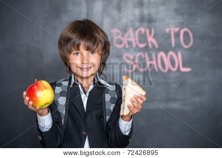 Close-up of little school boy with apple and sandwich near black