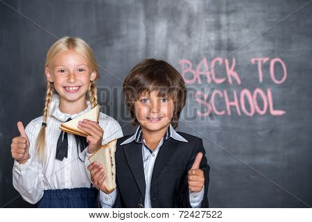 Close-up of happy school boy and girl with sandwiches near black