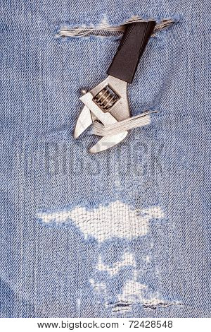 Pliers Black Handle Tool Pierce Through Old Blue Jeans Background.