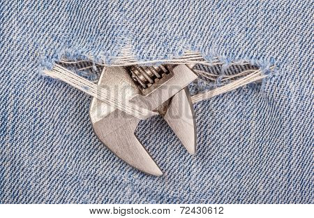 Head Of Pliers Black Handle Tool Pierce Through Old Blue Jeans Background.