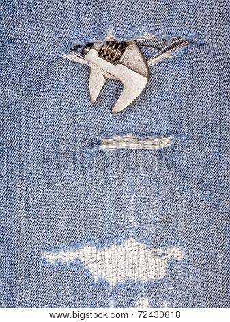 A Part Of Pliers Tool With Old Blue Jeans Background.