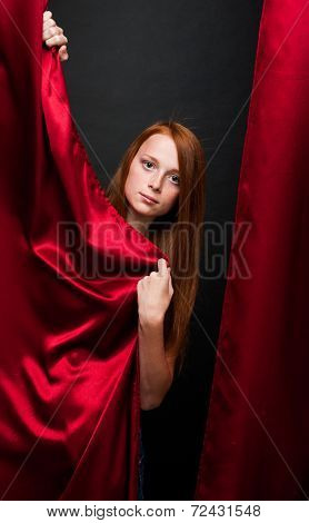 Beautiful Red-haired Girl With Red Curtains On A Dark Background