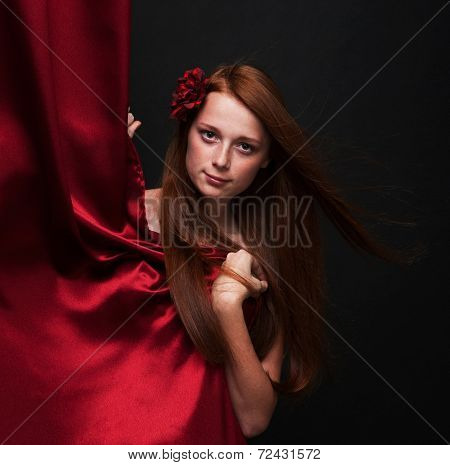 Beautiful Red-haired Girl Looks Out From Behind A Red Theater Curtain