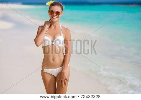 Woman in bikini at tropical beach.