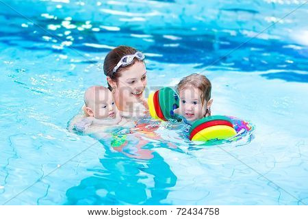 Young Active Mother Playing With Her Toddler Daughter And Baby Son In A Swimming Pool