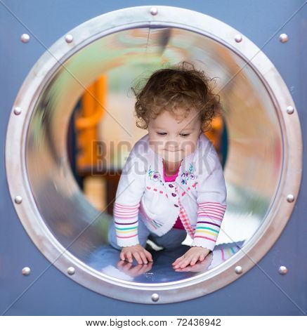 Cute Curly Baby Girl Climbing A Slide On A Playground