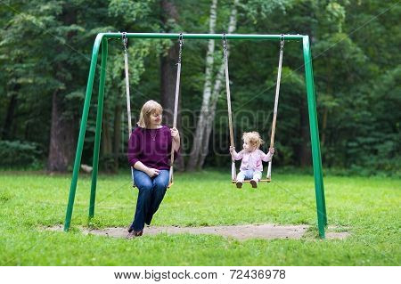 Happy Young Woman And A Little Baby Girl Swinging On A Playground