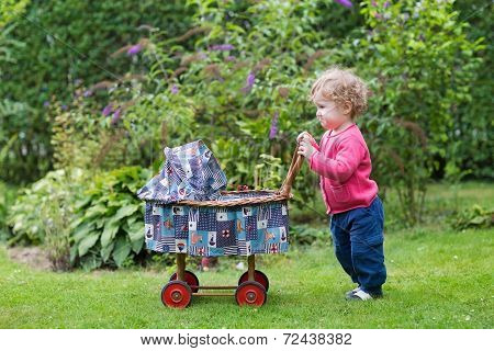 Funny Curly Baby Girl Playing With A Vintage Doll Stroller In The Garden