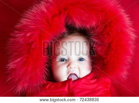 Funny Baby Girl With Beautiful Blue Eyes In A Warm Winter Jacket With Red Hood
