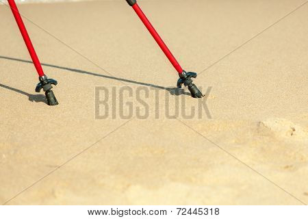 Nordic Walking Red Poles On The Sandy Beach