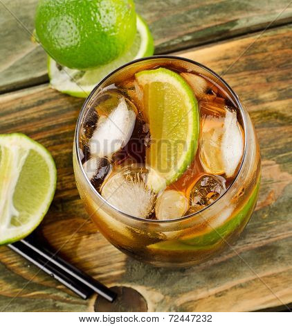Cuba Libre Drink With Lime On Wooden Table
