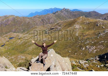 Young Happy Smiling Woman Sitting On Edge Of The Mountain