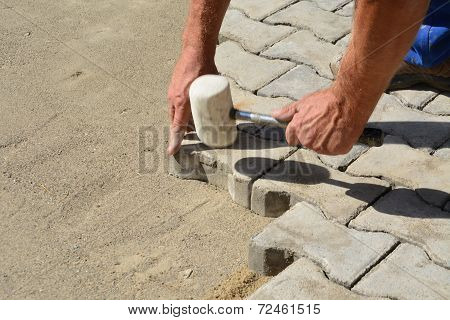 Worker Laying Interlocking Concrete Pavers