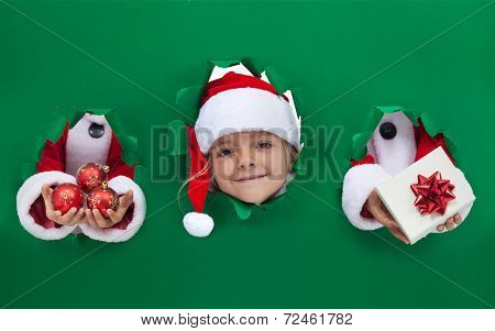 Christmas Girl Peeking Out From Hole In Wrapping Paper