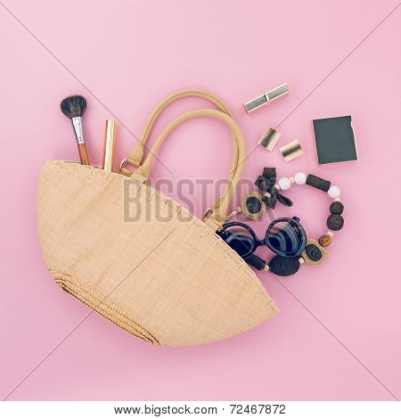 Ladies handmade bag with different accessories on pink background