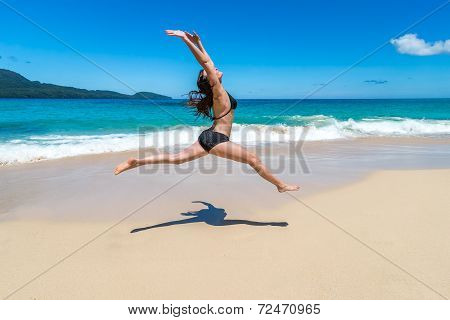 Beautiful girl in bikini jumping on tropical beach