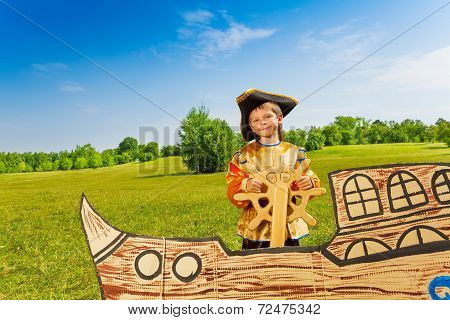 Smiling boy in pirate costume holds the helm