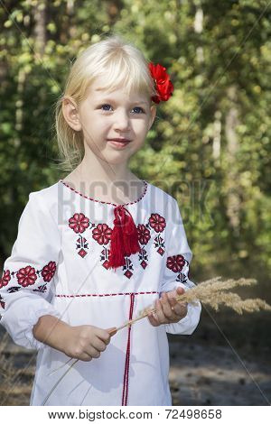 The Little Blue-eyed Blonde Standing In Embroidery In The Woods .