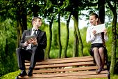 stock photo of work bench  - Young Business couple sitting on the bench and reading or working with tablets outdoors - JPG