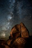 stock photo of nativity  - The Milky Way galaxy rises behind a rock covered with Native American petroglyphs near Gila Bend Arizona - JPG