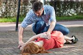 foto of accident victim  - Man lying unconscious girl in recovery position - JPG
