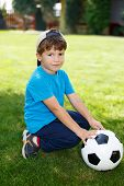 foto of ball cap  - Little boy in cap with soccer ball outdoor portrait - JPG