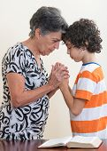 foto of praying  - Grandmother and grandson praying together in their daily Christian devotional - JPG
