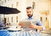 picture of internet-cafe  - Modern hipster businessman drinking espresso coffee in the city cafe during lunch time and working on tablet - JPG