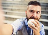stock photo of starving  - Modern hipster businessman having lunch break, sitting on stairs in town center and eating burger