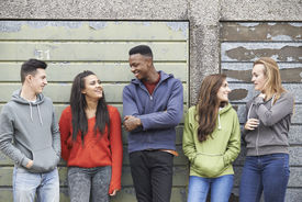 stock photo of gang  - Gang Of Teenagers Hanging Out In Urban Environment - JPG