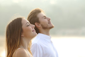 pic of deep  - Profile of a couple of man and woman breathing deep fresh air together at sunset - JPG