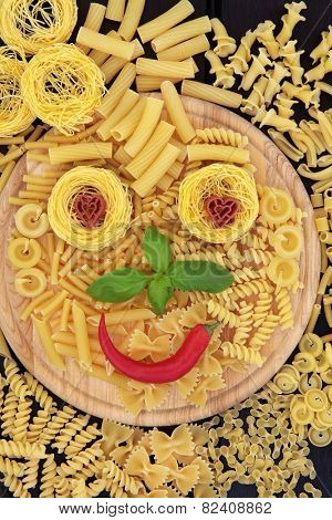 Pasta smiley face abstract background on a wooden board.