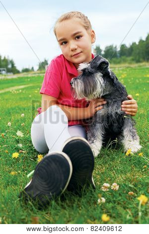 girl And Her Dog Lying On The Grass In The Park On A Summer Day