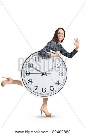 laughing woman with clock running, looking at camera and waving palm. isolated on white background